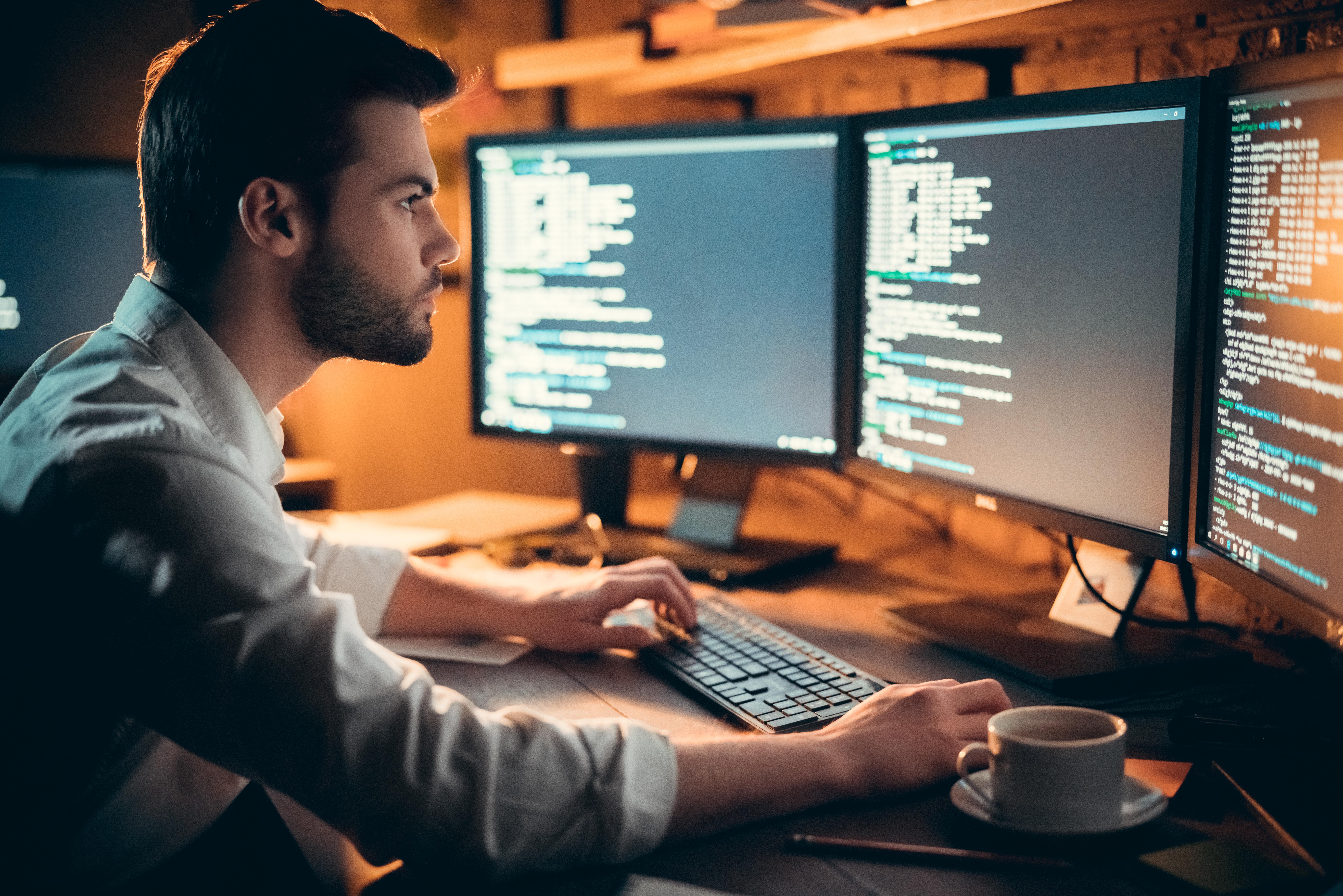 man looking at monitors
