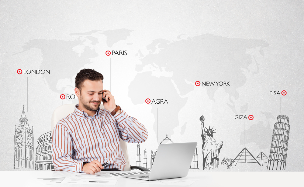 man on computer sitting in front of map