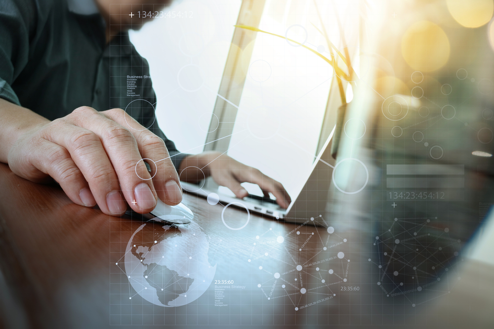 business man hand working on laptop computer with digital business strategy diagram on wooden desk as concept